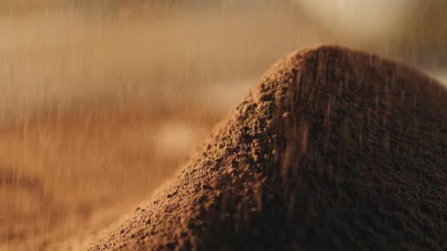 vídeos de stock e filmes b-roll de close-up of sifting cocoa powder sieve on a brown background - cacau em pó
