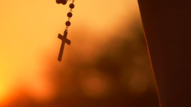 stockvideo's en b-roll-footage met close-up van silhouet kruis opknoping bij sunset - kerk