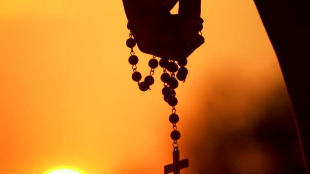 närbild av silhouette cross hängande vid solnedgången - krucifix bildbanksvideor och videomaterial från bakom kulisserna