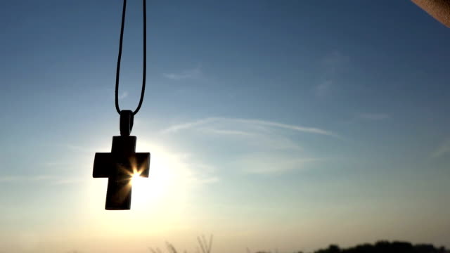 Closeup Of Silhouette Cross Hanging at sunset/sunrise time video