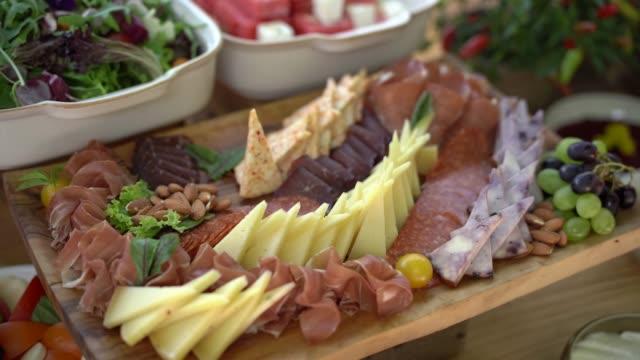 vídeos de stock, filmes e b-roll de close-up de queijo fatiado e prosciutto em uma tábua arborizada. - antepasto