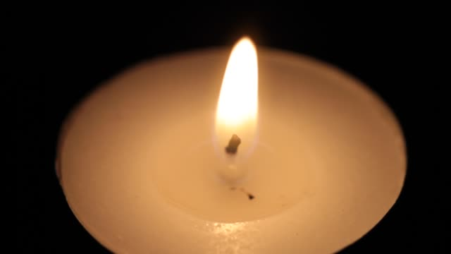 Close-up of small burning candle