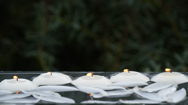 Close-up of small burning candles and lotus flower petals in water