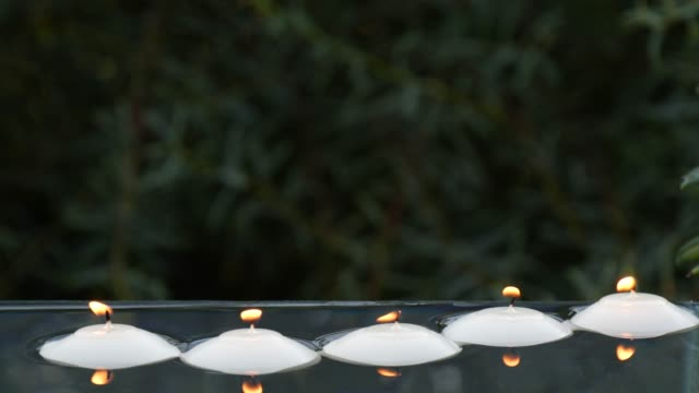 Close-up of small burning candles in water