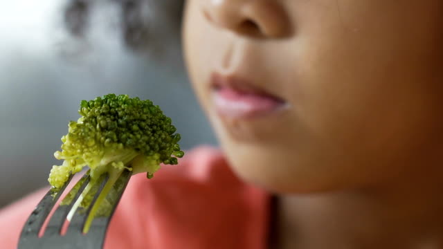 Close-up of small kid holding fresh green broccoli on fork, delicious vegetable video