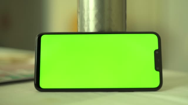 Close-up of smartphone chroma key green screen smartphone in office