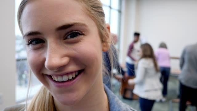 stockvideo's en b-roll-footage met close-up van lachende kaukasische tiener meisje gezicht - student