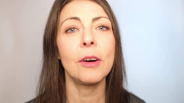 vidéos et rushes de plan rapproché de la femme adulte de milieu de sourire parlant - une seule femme d'âge mûr