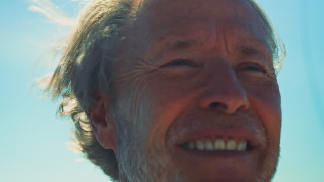 Close-up of smiling senior man looking away
