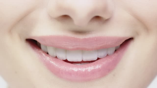 Close-up of smiling woman biting her glossy lips