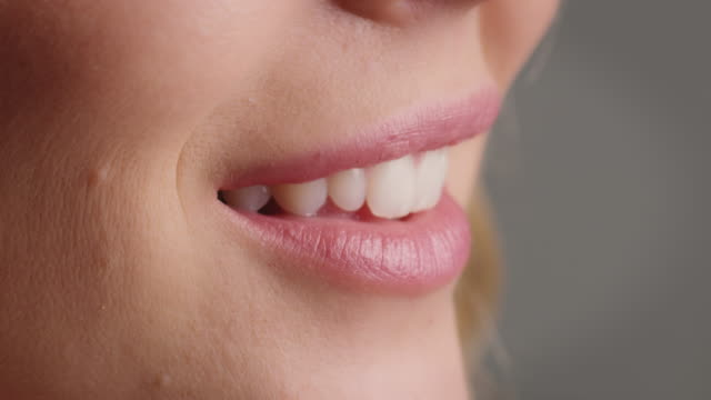 Close-up of smiling woman with pink lips