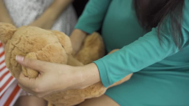Close-up of soft yellow teddy bear. Female hands holding the gift. Pregnant woman