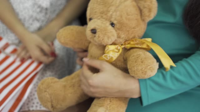 Close-up of soft yellow teddy bear with a silk bow. Female hands holding the gift. Pregnant woman