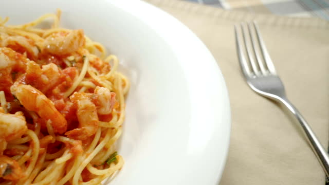 Close-up of spaghetti with shrimp. Seafood pasta on white plate. Slow motion. HD