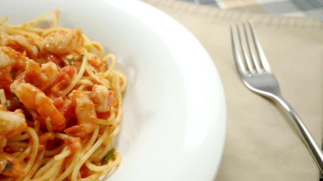 nahaufnahme von spaghetti mit garnelen. meeresfrüchte pasta auf weißem teller. zeitlupe. hd - fische und meeresfrüchte stock-videos und b-roll-filmmaterial