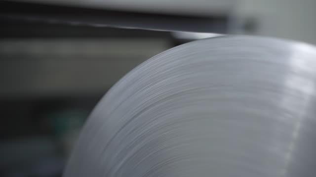 nahaufnahme von funkelnden aluminiumfolienblechen, die auf anlagen am produktionsband rollen. automatisierte maschinenverarbeitung von rohstoffen im werk. geschäft, fließband, fertigung. - aluminium stock-videos und b-roll-filmmaterial