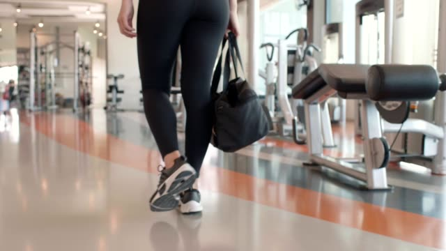 Closeup of sport woman lower body walking into fitness gym with outfit clothes bag for workout training. Sporty girl prepare to doing bodybuilding weight strength cardio inside club.