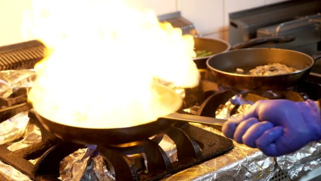 パンとオリーブ オイルを追加し、野菜と肉の混合物を炎のシェフとストーブのクローズ アップ - 異国情緒点の映像素材/bロール