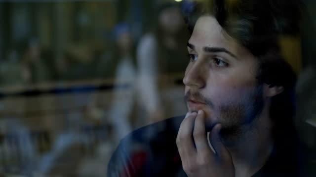 closeup of stressed business man thinking and sitting near glass window into a pub people passing by - nuda filmów i materiałów b-roll