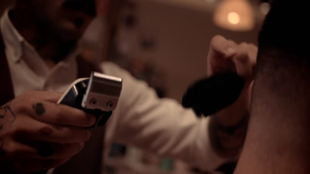 Close-up of stylish barber cutting man's hair with hair clipper video