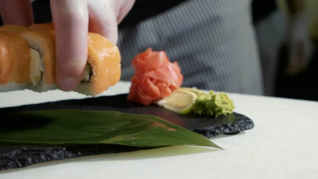 Close-up of sushi chef in gloves puts the rolls on decorated plate. video