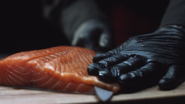 Close-up of sushi chef in gloves slices fresh salmon at sushi bar. Slicing salmon fillets
