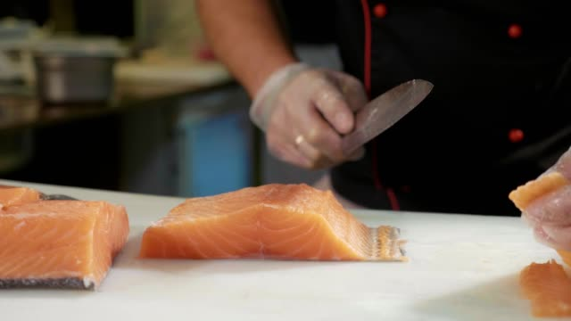 Close-up of sushi chef in gloves slices fresh salmon at sushi bar. Close-up of sushi chef in gloves slices fresh salmon at sushi bar. Professional cook cutting fish fillet at commercial kitchen, slow motion. sashimi stock videos & royalty-free footage