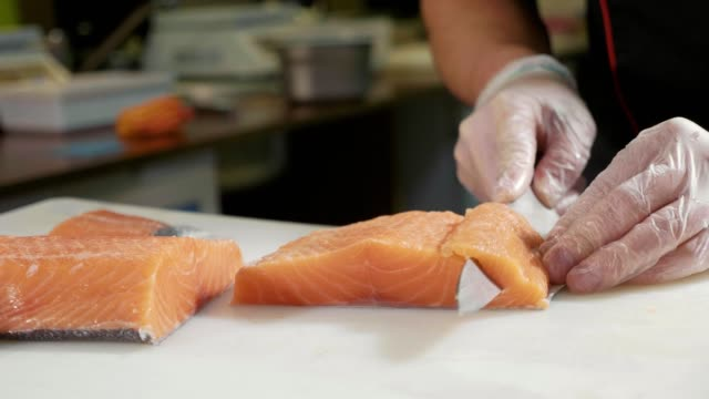 Close-up of sushi chef in gloves slices fresh salmon at sushi bar. video