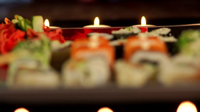 Close-up of sushi with candles in the background. video