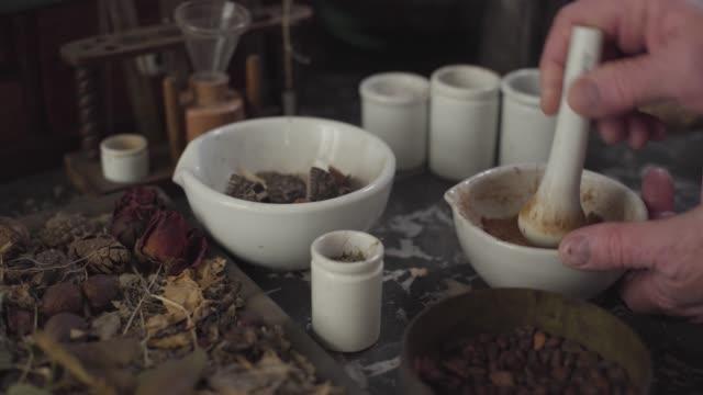 närbild av bord med torkade blommor och vintage kemiska behållare. gamla manliga kaukasiska händer slipning pulver med murbruk och mortelstöt. ancient apothecary, alternativ medicin, retro, sjukvård. - forntida bildbanksvideor och videomaterial från bakom kulisserna