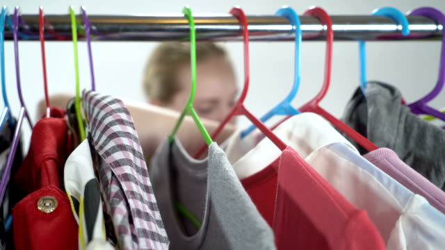 Closeup of teenage girl thinking what to dress in closet room video