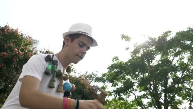 vídeos y material grabado en eventos de stock de closeup del colector de juguete kendama adolescentes ejercer trucos al aire libre en cámara lenta - coordinación