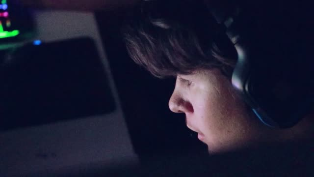 Close-up of Teenager Playing Video Games with his online friends Boy Gamer Plays in Video Game on a eSports Tournament. He is focused in game. He wears Headphones and Speaks into Microphone. donna stock videos & royalty-free footage