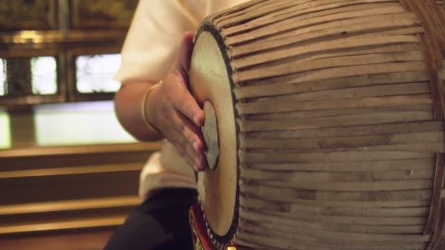 vidéos et rushes de gros plan de musicien thaïlandais jouant puang-mang - instrument à percussion
