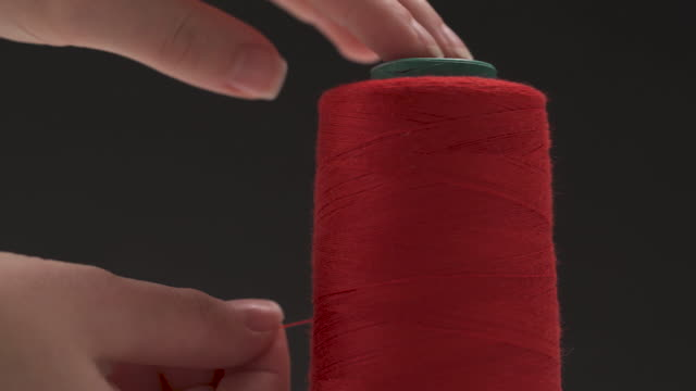a close-up of the bobbin with red thread and a hand holding it to the top starts unwinding the thread; then cuts it off with scissors - cilindro video stock e b–roll