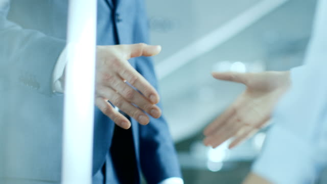 vídeos de stock e filmes b-roll de close-up of the businesswoman and businessman shaking hands with emphasis on the handshake. - parceria