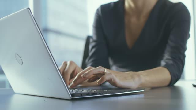 Primer plano de manos de la empresaria escribiendo en un ordenador portátil en su oficina. - vídeo
