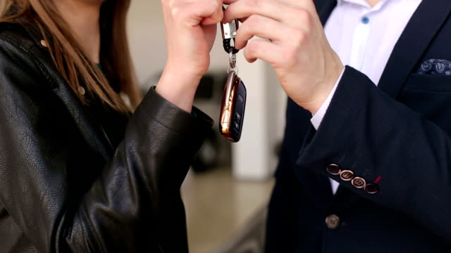 Close-up of the car salesman gives the girl the keys to the new car.