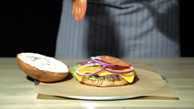 Close-up of the chef's hands preparing the burger. Close-up of the chef's hands preparing the burger. bun bread stock videos & royalty-free footage