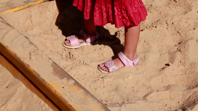 Close-up of the child's feet in the sandbox Feet close-up of a little girl in red dress walking on the sand in the sandbox stamping feet stock videos & royalty-free footage