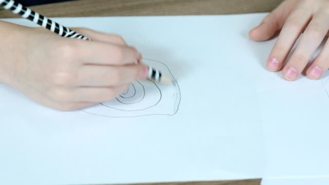 Close-up of the child's hands are drawn with a simple pencil on white paper. Top view. video