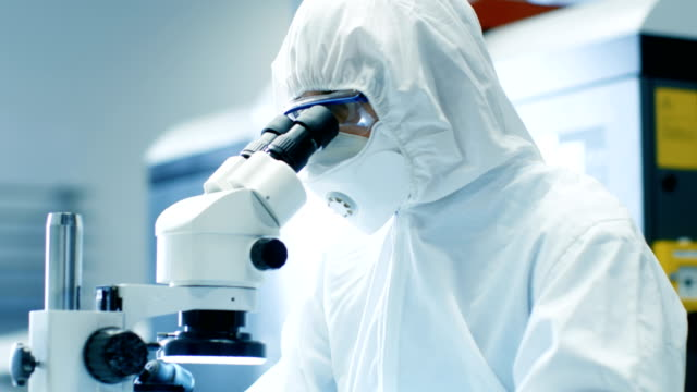 close-up of the engineer/ technician/ scientist checking component under the microscope. he wears sterile coverall suit and protective glasses while working a project. - igiene video stock e b–roll