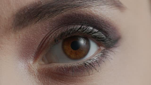 stockvideo's en b-roll-footage met close-up van de eyeliner wordt toegepast op het ooglid van de vrouw en het oog opent. - eyeliner
