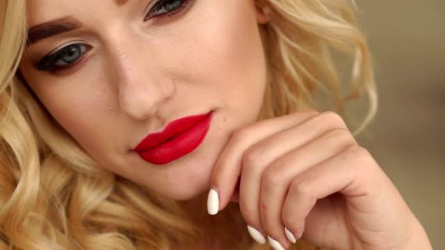 vidéos et rushes de plan rapproché du visage d'une fille avec des yeux bleus avec le renivellement lumineux et les lèvres rouges. - rouge à lèvres rouge