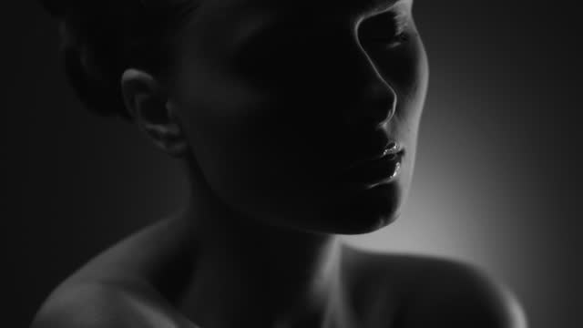 Close-up of the face of a naked girl who slowly turns it around and the camera approaches her. Black and white video. video