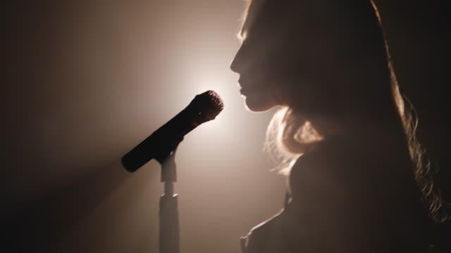 närbild av ansiktet på sångaren med mikrofon på en svart rökig bakgrund. sångaren sjunger en låt på scenen i mörkret, rök, lila ljus, konsert - sångare artist bildbanksvideor och videomaterial från bakom kulisserna