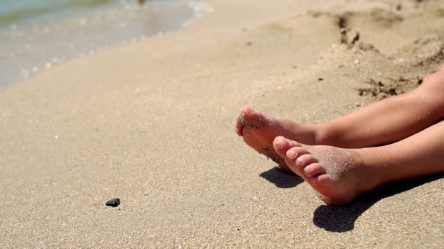 close-up of the feet of a small child on the seashore in the sand slow motion. - dito del piede video stock e b–roll