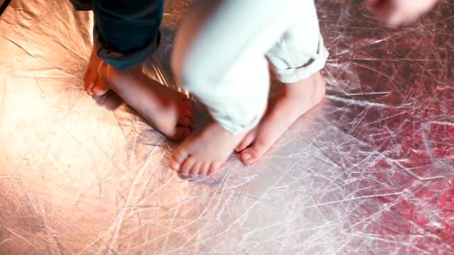 nahaufnahme der füße von kindern, die tanzbewegungen auf einem glänzenden boden. - mittelstufenlehrer stock-videos und b-roll-filmmaterial