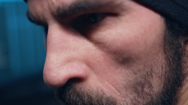 Close-up of the hacker's terrified eyes, which constantly turns around, he is afraid that now he will be discovered.