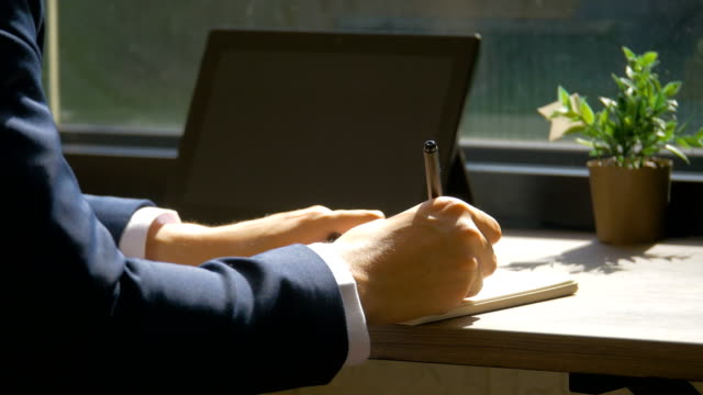 close-up of the hands of a businessman writing a document on book in coffee shop on early morning, business people concept - promemoria video stock e b–roll